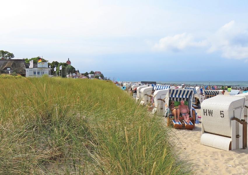 2018-08-17 mittags, Kühlungsborn, Strandkörbe am Strandzugang 17, Blickrichtung West, zum Baltic Platz (Seebrückenvorplatz)